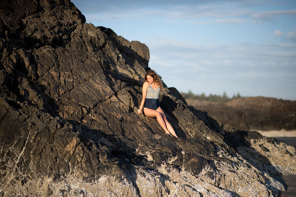 girl sitting on Incinerator Rock at Long Beach in Tofino in Monaia swimsuit. Photographed by Tofino photographer Kaitlyn Shea.