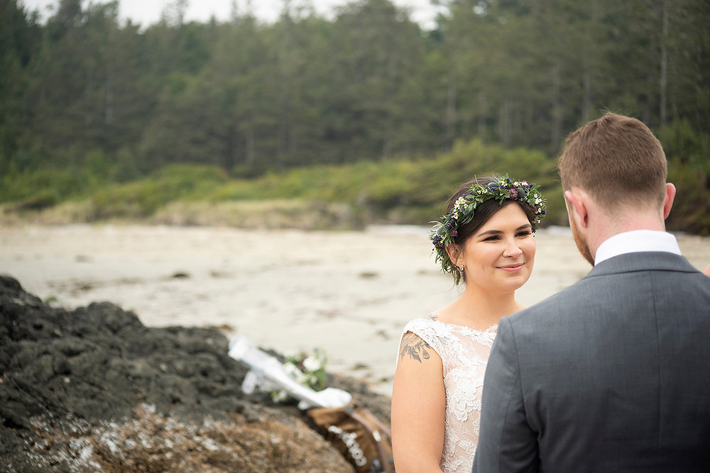 bride smiles at groom at small beach wedding at Schooner Cove Tofino. Photographed by Kaitlyn Shea