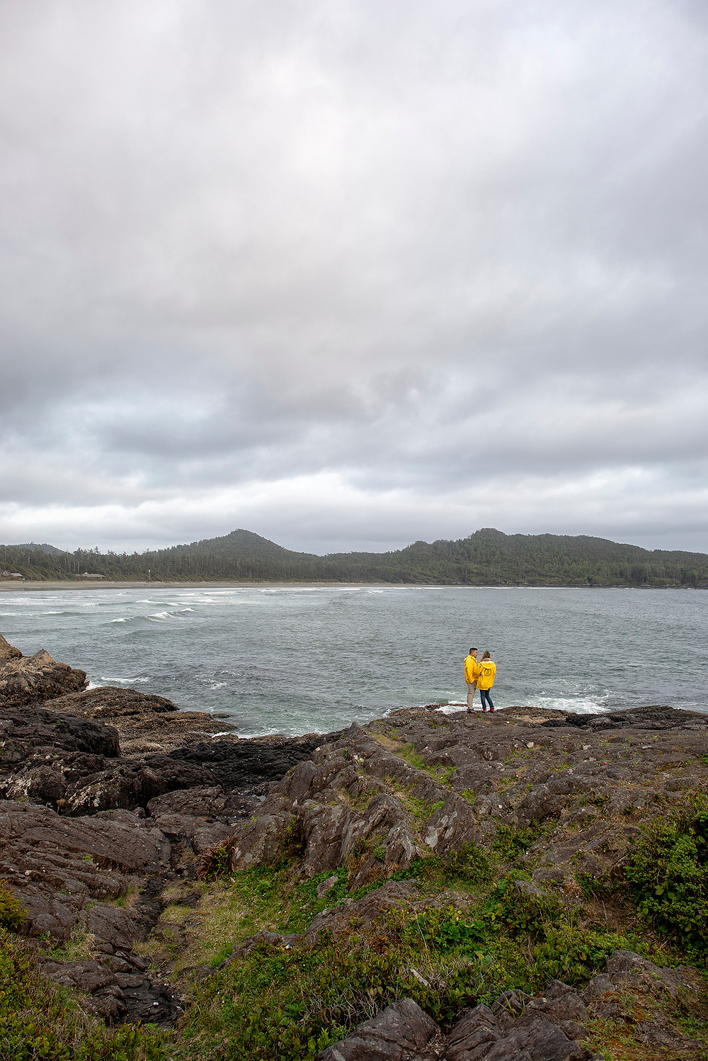 Engaged couple admires views from Pettinger Point after surprise proposal in Tofino. Photographed by Kaitlyn Shea.