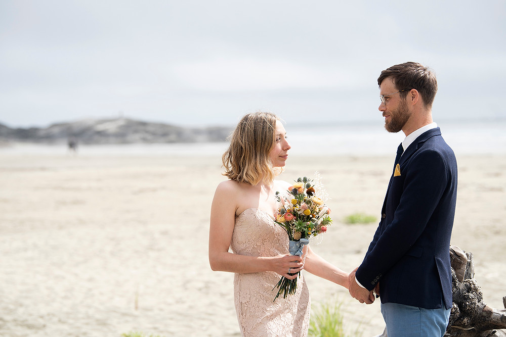Couple recite their vows at their Tofino beach elopement. Photograped by Kaitlyn Shea.