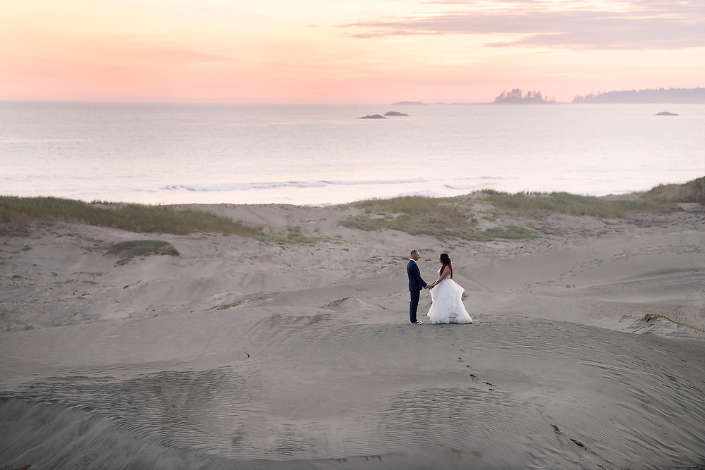 Bride and groom hold hands in the dunes during their sunset wedding photos in Tofino. Photographed by Kaitlyn Shea.