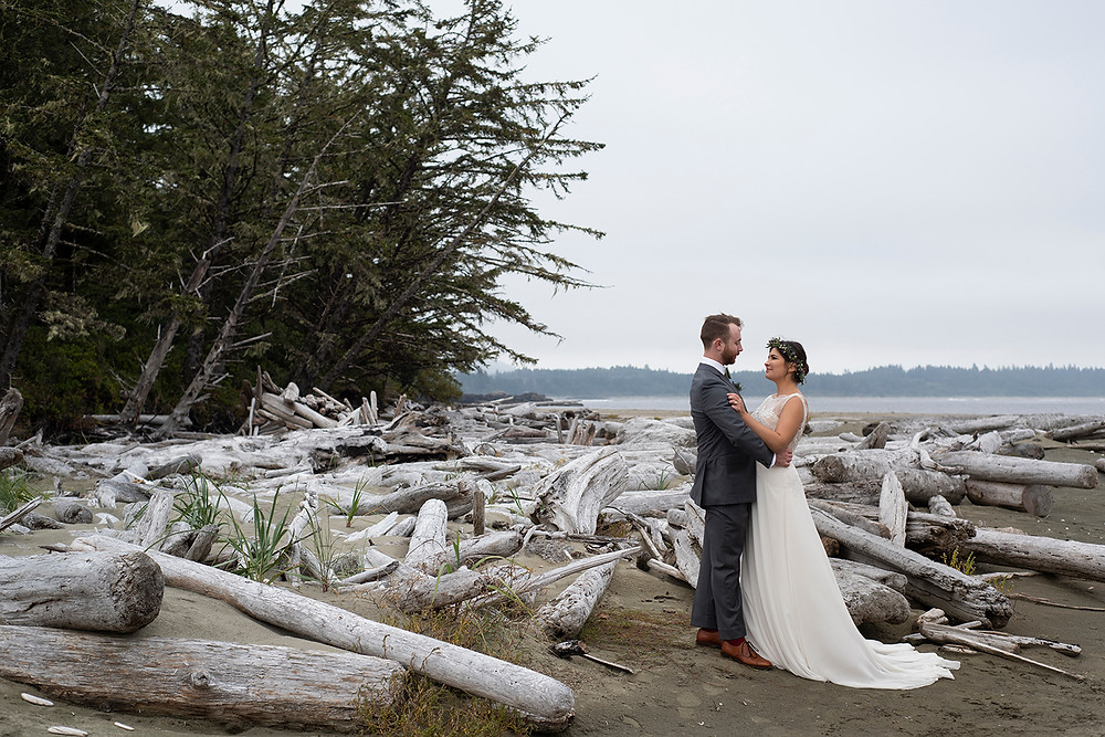 bride and groom standing by driftwood at Schooner Cove wedding in Tofino. Photographed by Kaitlyn Shea