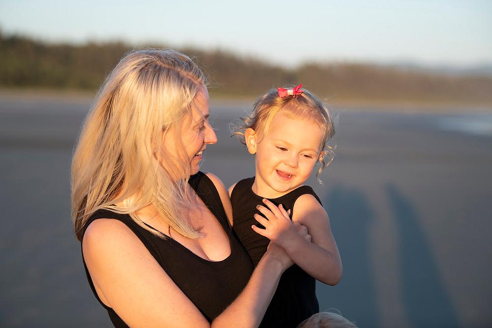 Mom hugs daughter tight during family photos in tofino. photographed by Tofino photographer Kaitlyn Shea.