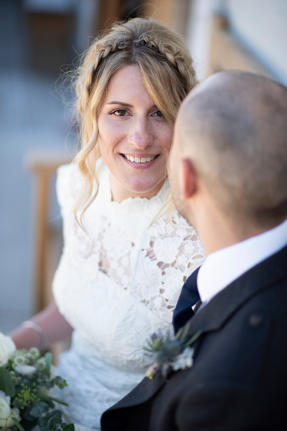 Bride smiles while sitting on a bench with her love at Sea Cider on Vancouver Island. Photographed by Kaitlyn Shea.