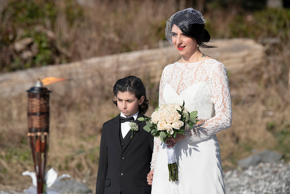 Bride sees groom while she walks down the aisle at their Ucluelet elopement. Photographed by Kaitlyn Shea.
