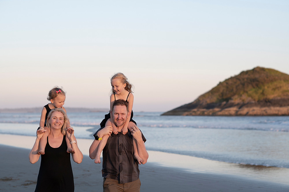 Parents carry daughters on their shoulders during family photos in Tofino. Photographed by Kaitlyn Shea.