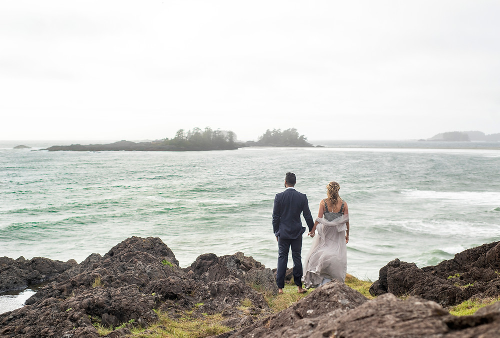 Couple holds hands and looks out at the ocean at their small wedding in Tofino. Photographed by Tofino wedding photographer Kaitlyn Shea.