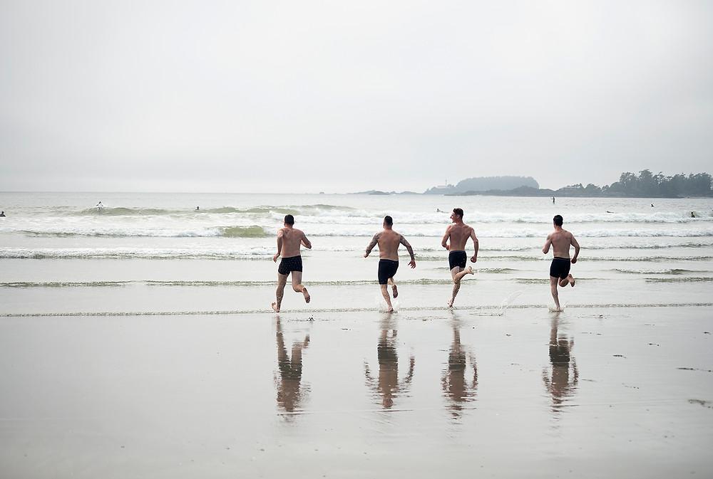 groomsmen run into ocean at Tofino beach wedding