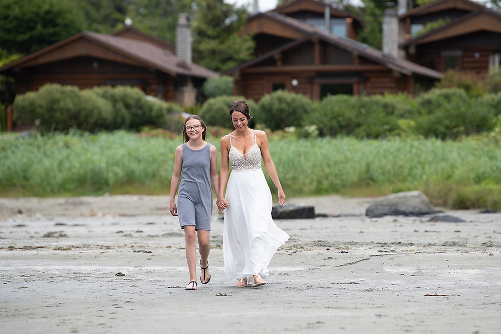 Bride walks down beach toward her groom at Elopement in Tofino. Photographed by Kaitlyn Shea.