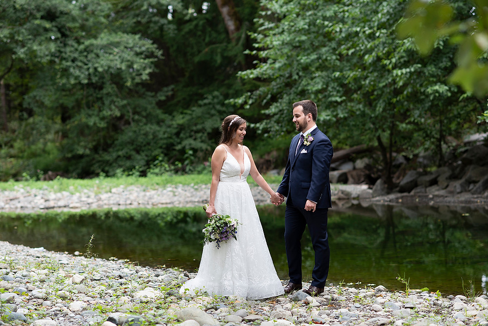 Happy couple standing beside a beautiful creek in port Alberni at their Vancouver Island wedding. Photographed by Kaitlyn Shea.
