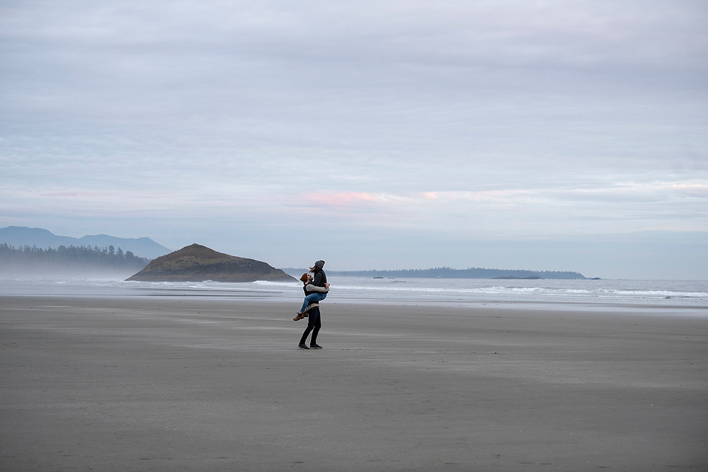 Girl jumps into her fiancé's arms during engagement photos on the beach in Tofino. Photographed by Kaitlyn Shea.
