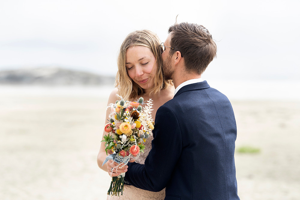 Groom kisses bride on the cheek at their Tofino elopement on the beach. Photographed by Kaitlyn Shea.