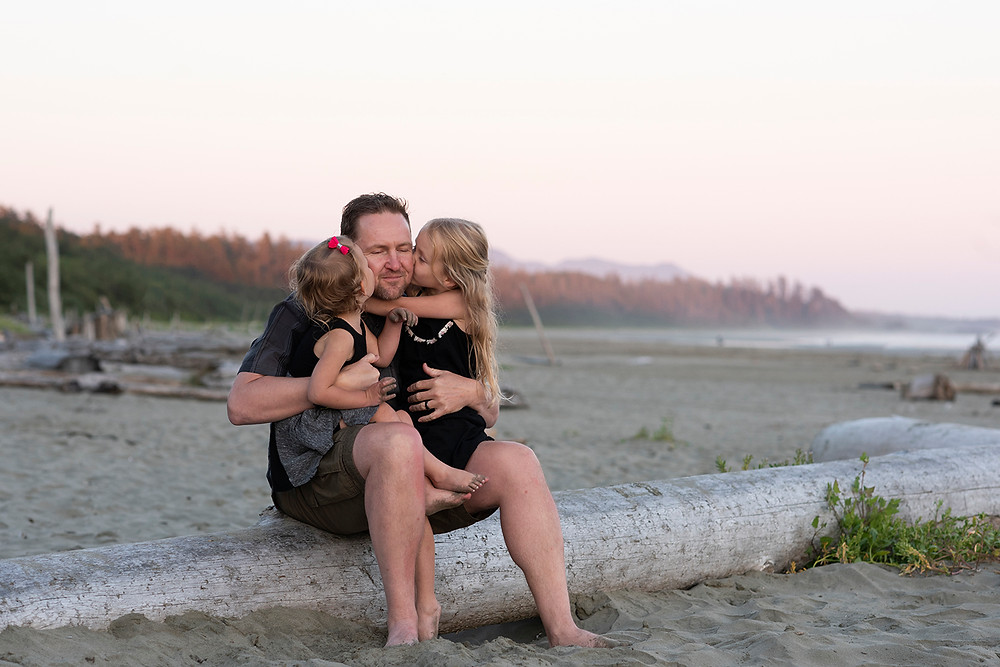 Daughters kiss dad on the cheek during family photos in Tofino. Photographed by Kaitlyn Shea.