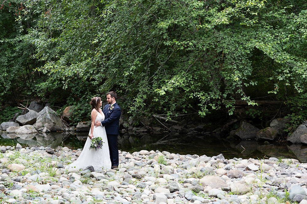 Bride and groom embrace at a creekside at their Vancouver Island wedding in Port Alberni. Photographed by Kaitlyn Shea.