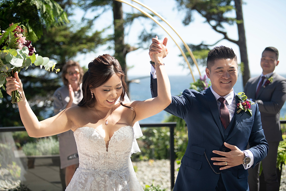 Bride and groom raise hands in excitment at their Ucluelet wedding at Black Rock Resort. Photographed by Ucluelet Photographer Kaitlyn Shea.