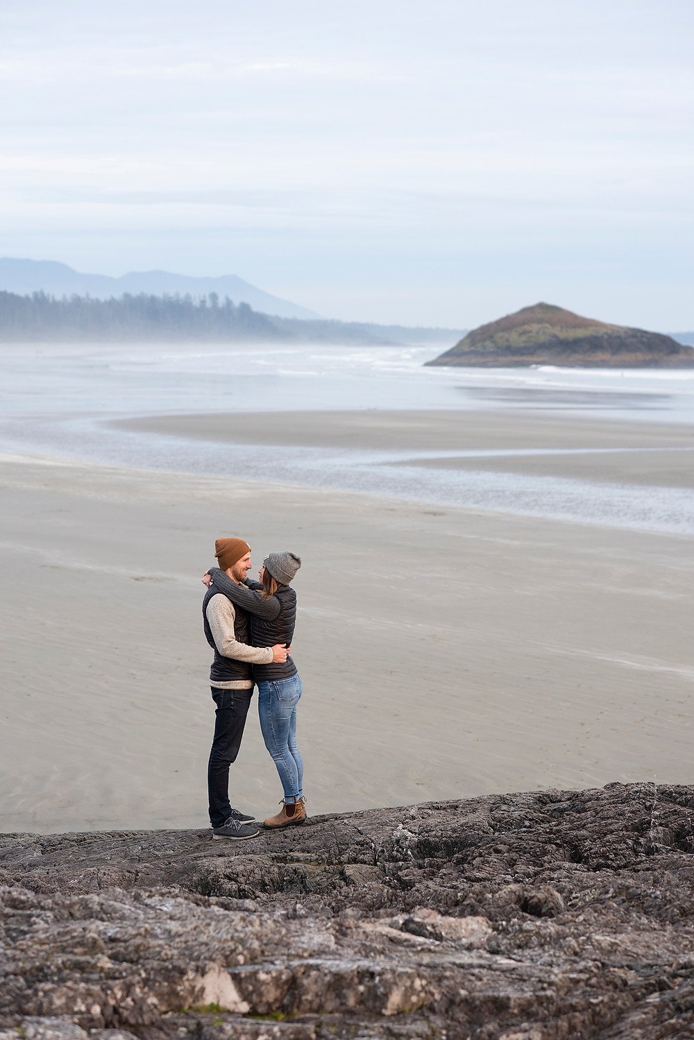 Man and woman embrace during engagement photo session on the beach in Tofino. Photographed by Kaitlyn Shea.