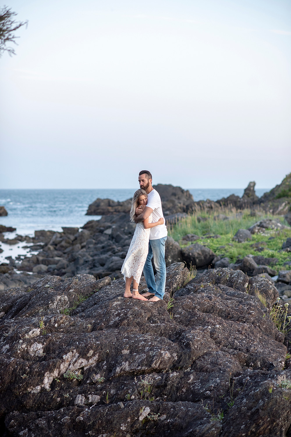 Couple hugs with sunset behind them during their engagement photos in Ucluelet. Photographed by Tofino photographer Kaitlyn Shea.