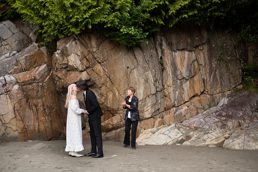 Couple has their first kiss as a married couple at their Tofino wedding at tonquin Beach. Photographed by Tofino wedding photographer Kaitlyn Shea.