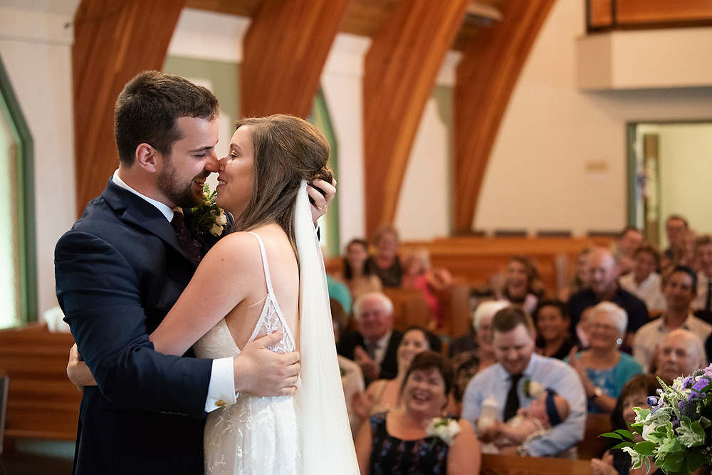 First kiss as a married couple at August wedding on Vancouver Island. Photographed by Kaitlyn Shea.