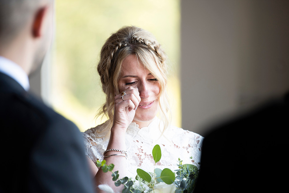 Bride wipes away tear during wedding ceremony at Sea Cider in Victoria. Photographed by Kaitlyn Shea.