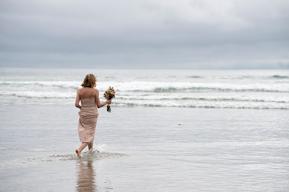 Bride runs into the water at her Tofino elopement. Photographed by Kaitlyn Shea.