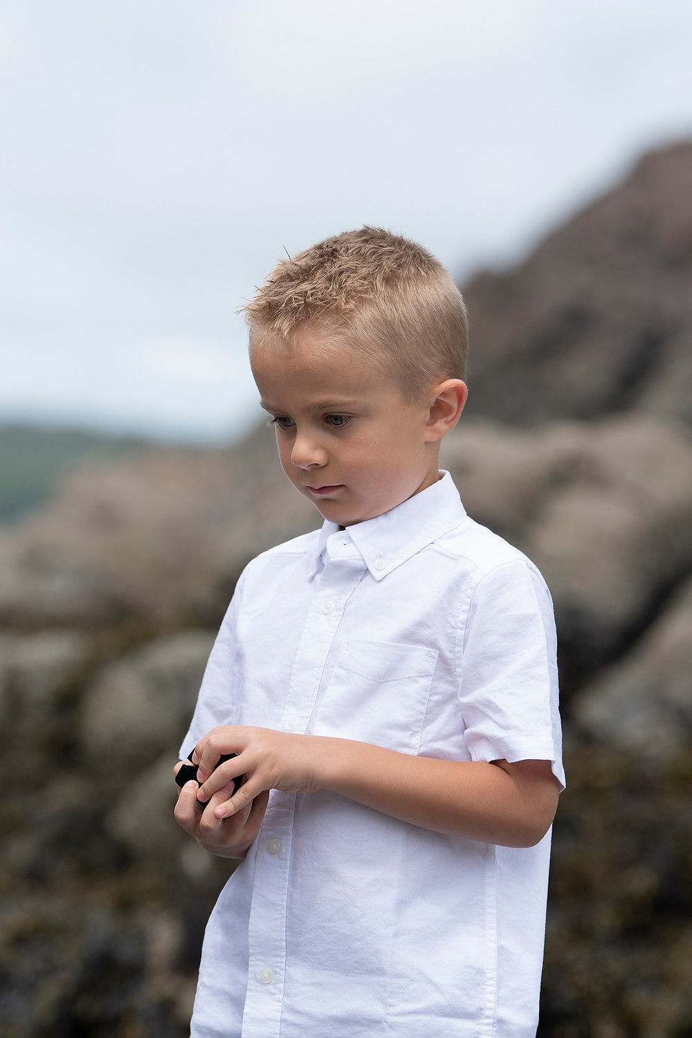 Little boy holds wedding rings at an elopement in Tofino. Photographed by Kaitlyn Shea.