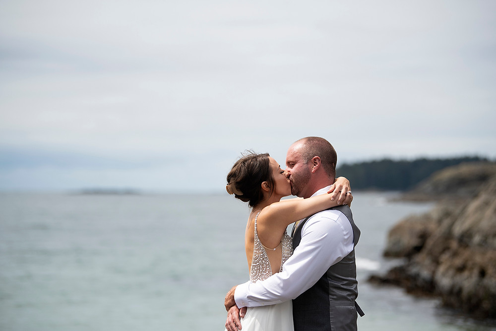 Bride and groom have their first kiss at an Beautiful beach ceremony at an Bride and groom hold rings during an elopement in Tofino. Photographed by Kaitlyn Shea.
