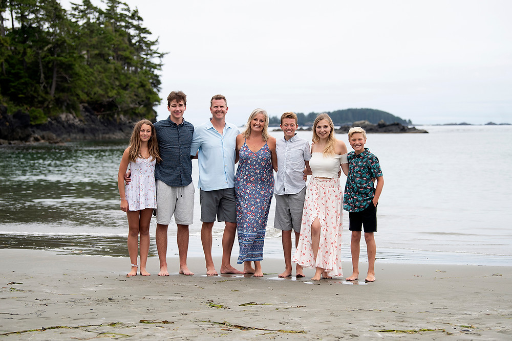 Happy family standing together on Middle Beach in Tofino. Photographed by Kaitlyn Shea.