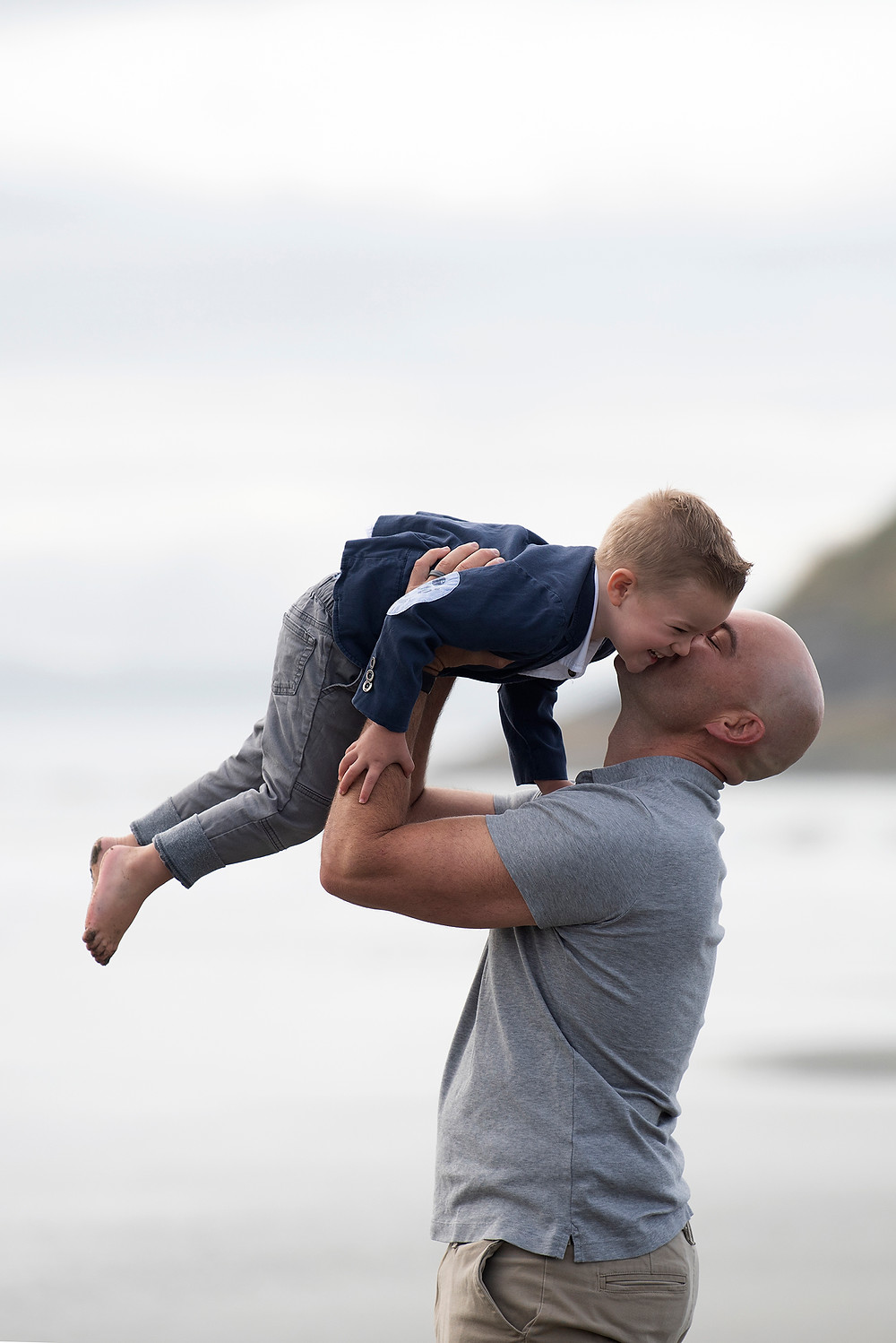 Father holds son in the air during a family photography session. Photographed by Kaitlyn Shea.