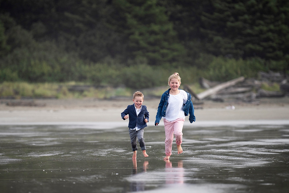 Kids run on Long beach during their family photography session in Tofino. Photographed by Kaitlyn Shea.