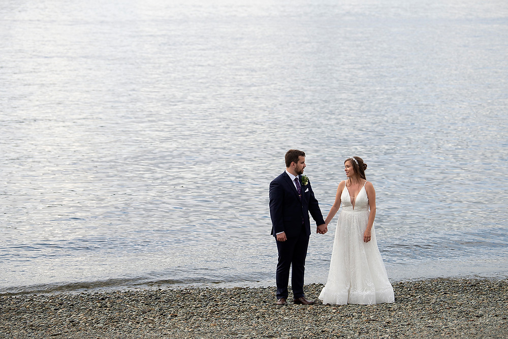 Newly married couple stand on the beach in Port Alberni at their August wedding on Vancouver Island. Photographed by Kaitlyn Shea.