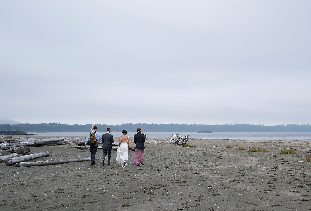 friends walk down the beach at wedding at Schooner Cove Tofino. Photographed by Kaitlyn Shea