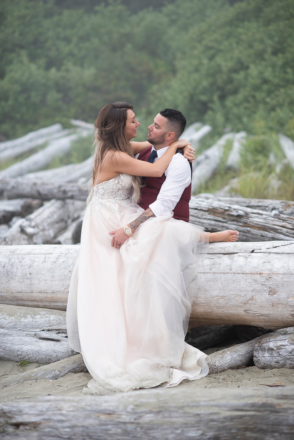 bride sits on groom and looks into his eyes at Tofino beach wedding. Photographed by Kaitlyn Shea