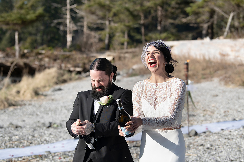 Bride and groom pop champagne at their Ucluelet elopement. Photographed by Kaitlyn Shea.