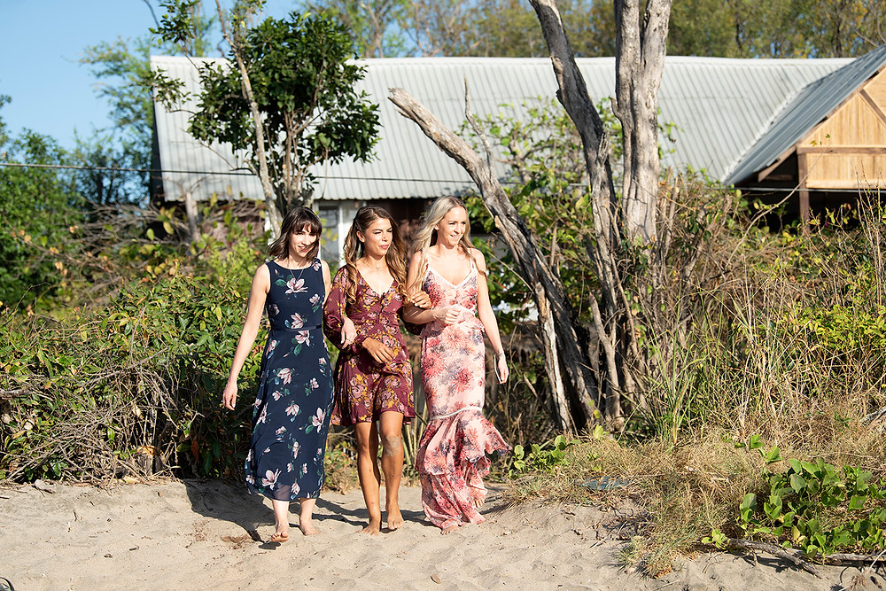 Bridesmaids walk down aisle at a destination wedding in Playa Grande, Costa Rica. Photographed by Kaitlyn Shea.