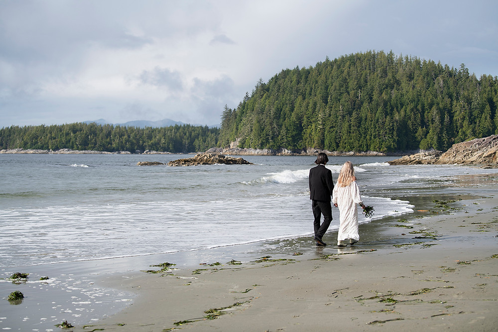Couple walks down the beach at their Tofino wedding at Tonquin Beach. Photographed by Tofino wedding photographer Kaitlyn Shea.