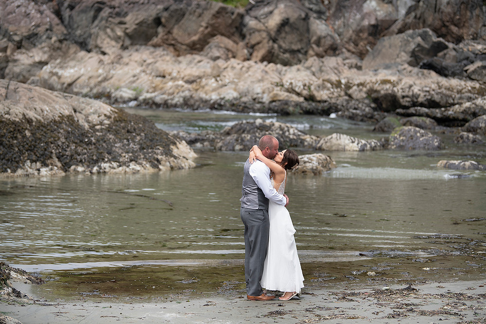 Married couple kisses on the beach at an Bride smiles at groom at an Newly weds kiss in the forest at an Couple embraces in the fporest at an Bride and groom have their first kiss at an Beautiful beach ceremony at an Bride and groom hold rings during an elopement in Tofino. Photographed by Kaitlyn Shea.