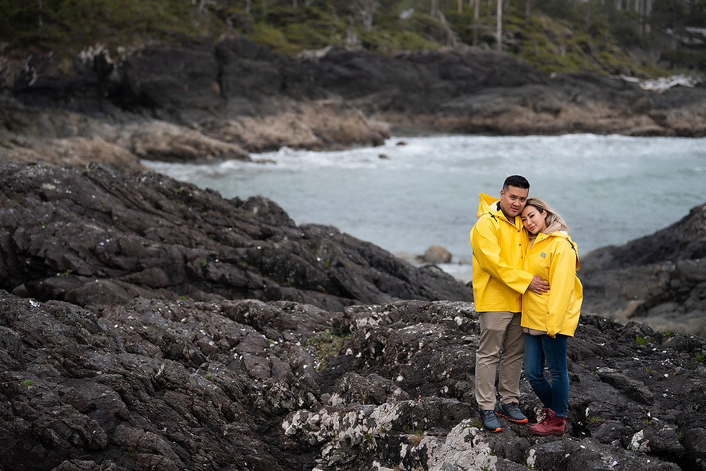 Newly engaged couple smiles for the camera on Pettinger Point in Tofino. Photographed by Kaitlyn Shea.