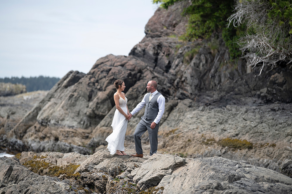 Bride smiles at groom at an Newly weds kiss in the forest at an Couple embraces in the fporest at an Bride and groom have their first kiss at an Beautiful beach ceremony at an Bride and groom hold rings during an elopement in Tofino. Photographed by Kaitlyn Shea.