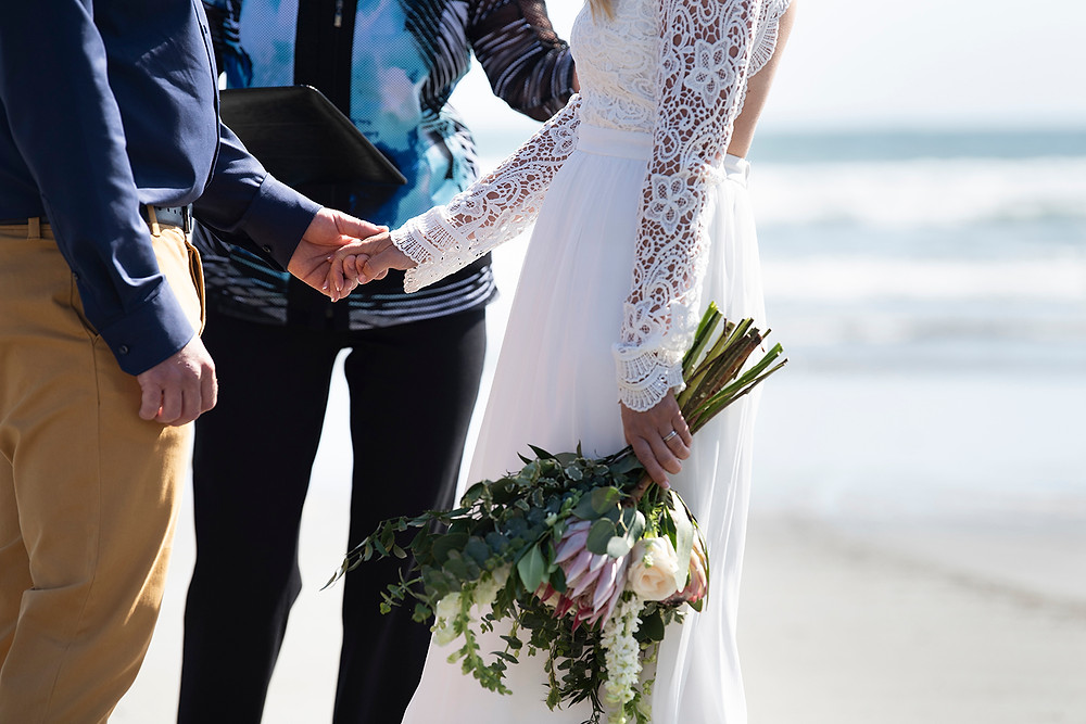hand holding at small Tofino beach wedding. Photographed by Kaitlyn Shea
