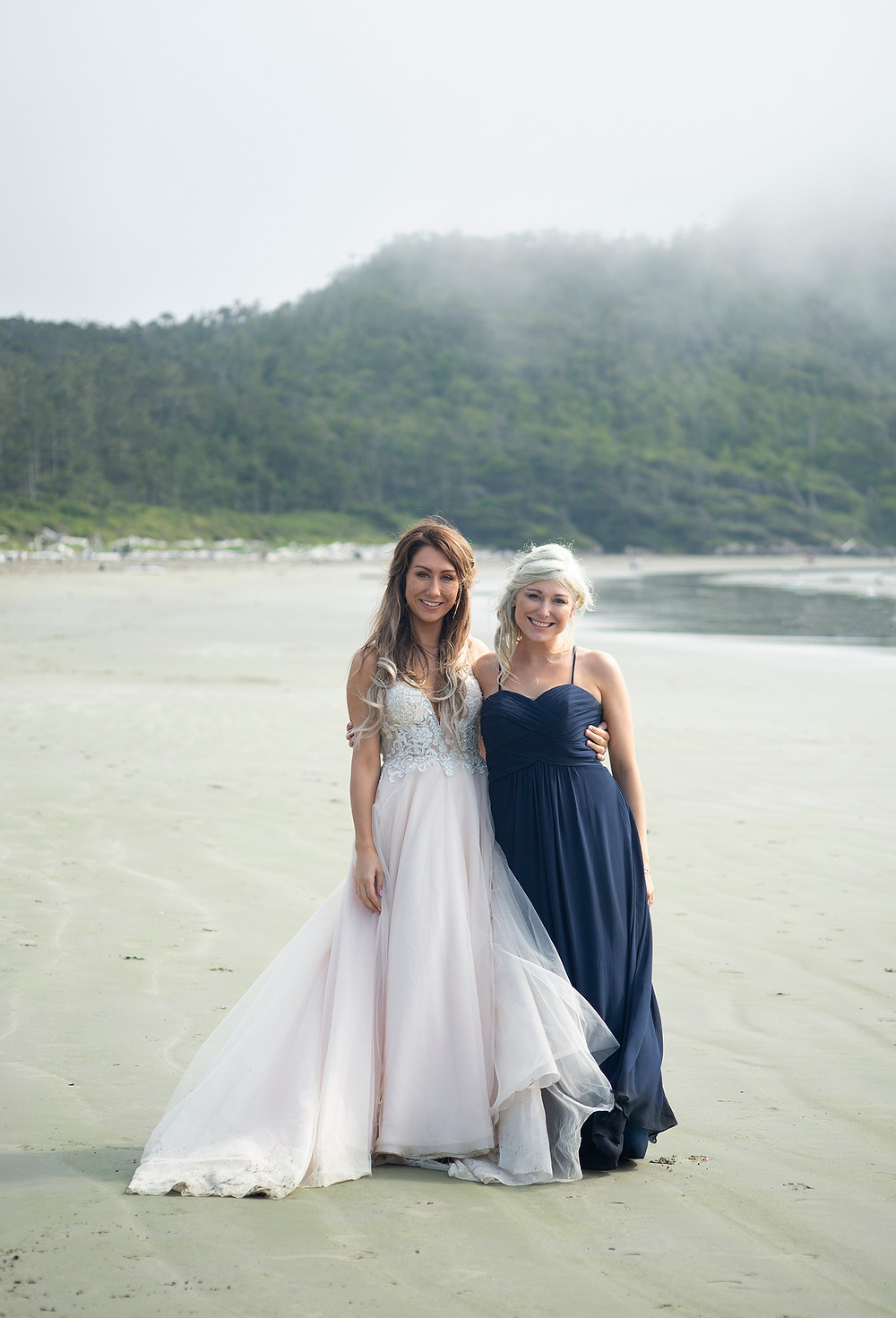 bride and her sister on the beach at Long Beach Lodge Tofino. Photographed by Kaitlyn Shea