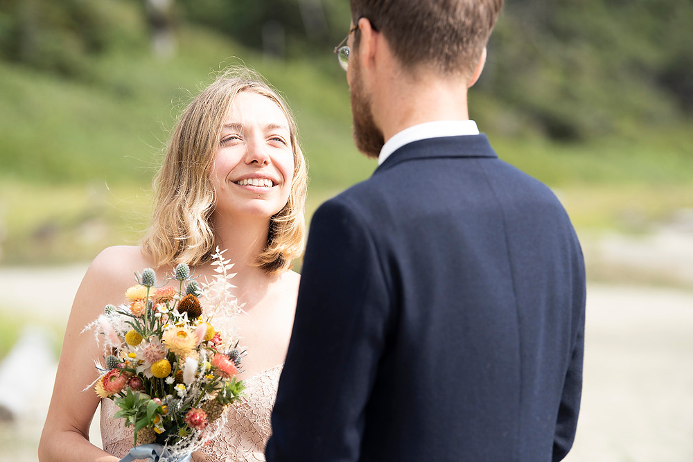 Bride smiles at groom at Tofino elopement. Photographed by Kaitlyn Shea.