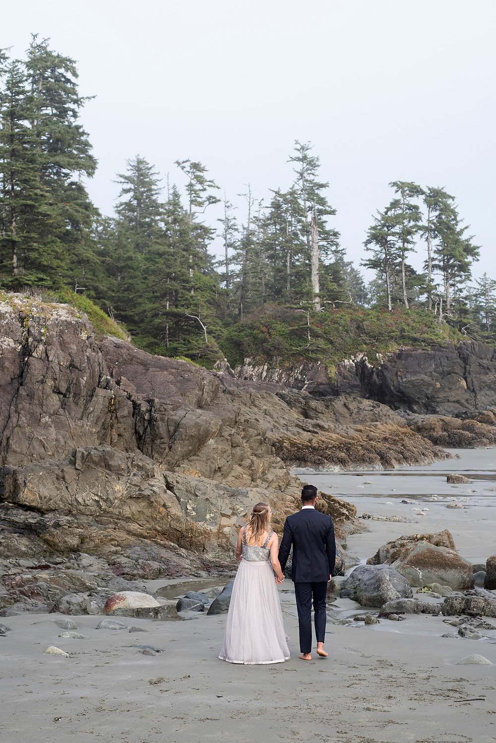 Couple walks on the beach at their small wedding in Tofino. Photographed by Tofino wedding photographer Kaitlyn Shea.