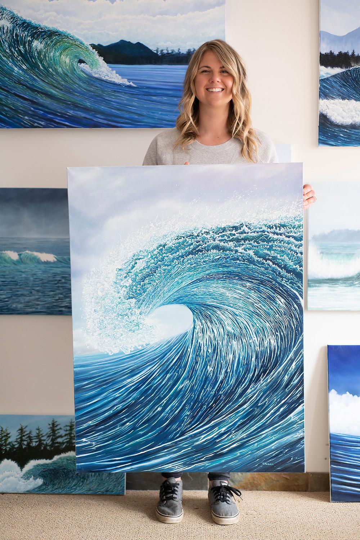Tofino artist Emma Paveley holding her oil painting Blue Behemoth