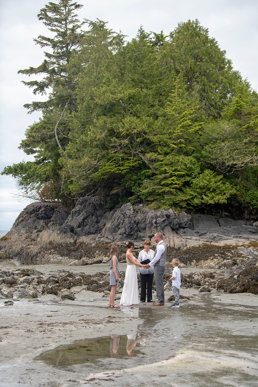 Beautiful beach ceremony at an Bride and groom hold rings during an elopement in Tofino. Photographed by Kaitlyn Shea.