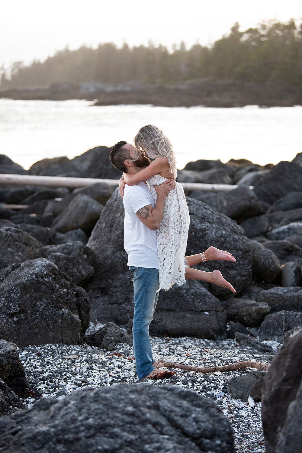 Man lifts woman up for a kiss during their engagement photos in Ucluelet. Photographed by Tofino photographer Kaitlyn Shea.