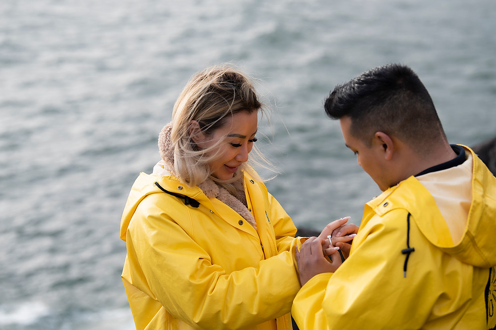 Man places engagement ring on woman's finger at surprise proposal in Tofino. Photographed by Kaitlyn Shea.