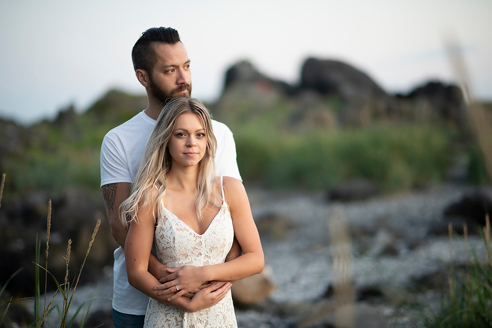 Man wraps his fiancé in a hug during their engagement photos in Ucluelet. Photographed by Tofino photographer Kaitlyn Shea.