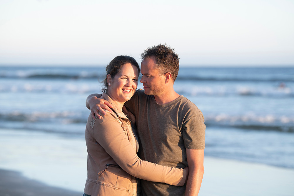 Couple shares a hug on Long beach during their Tofino family photos. Photographed by Kaitlyn Shea.