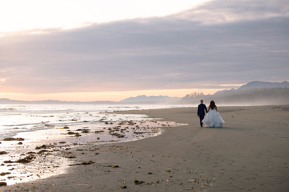 Couple walk on the beach at sunset in Tofino. Photographed by Kaitlyn Shea.